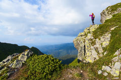 Sporty girl at the edge of precipice high on the mountains Stock Image