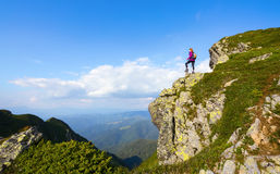 Sporty girl at the edge of precipice high on the mountains. Stock Image