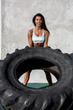Sporty girl exercise with big tire. Beautiful young woman in bright sexy shorts with pretty athlete muscular body lift up big heavy tire with happy smile Stock Photography