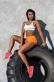 Sporty girl exercise with big tire. Beautiful young woman in bright sexy shorts with pretty athlete muscular body sit on big tire after long workout. Crossfit Stock Photos