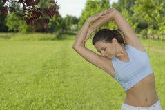 Sporty girl exercising on meadow against the sky.  Stock Photography
