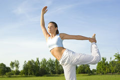 Sporty girl exercising on meadow against the sky Stock Images