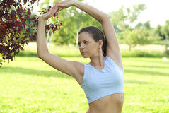 Sporty girl exercising on meadow against the sky.  royalty free stock photos