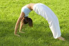 Sporty girl exercising on meadow against the sky royalty free stock photo