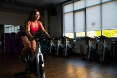 Sporty girl in fitness hall on cycle. Photo Stock Photos