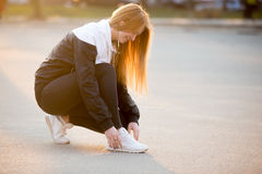Sporty girl fixing laces on sneakers Royalty Free Stock Photos