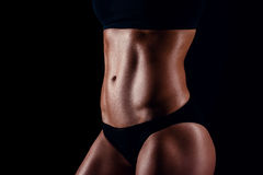 Sporty girl with great muscles in black sportswear. Tanned young athletic woman. A great sport female body. Royalty Free Stock Photos