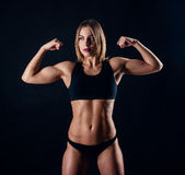 Sporty girl with great muscles in black sportswear. Tanned young athletic woman. A great sport female body. Muscular build female after workout Royalty Free Stock Image