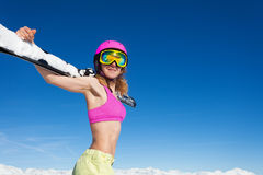 Sporty girl in helmet with skis against blue sky Stock Photography