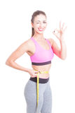 Sporty girl holding centimeter winking and smiling royalty free stock photos