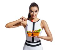 Sporty girl holding container with healthy nutrition. Photo of fitness model in fashionable sportswear isolated on white background. Healthy nutrition Stock Image