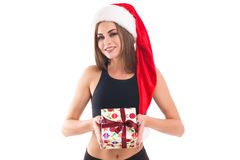 Sporty girl holding a gift on white isolated background. Sporty beautiful girl in a Christmas hat is holding a gift on a white isolated background Royalty Free Stock Photography