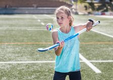 Sporty girl hopping a hockey ball on her hockey stick. Royalty Free Stock Photography