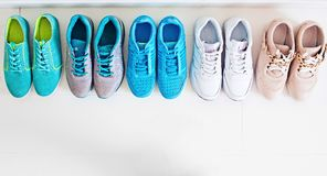 Choosing sports shoes. A sporty girl in jeans chooses which sneakers to go for training. Several pairs of sports shoes and legs Royalty Free Stock Photo