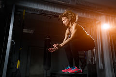 Sporty girl jumping over some boxes in a cross-training gym. Sporty girl blonde jumping over some boxes in a cross-training gym royalty free stock images