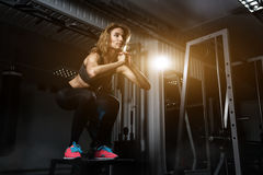 Sporty girl jumping over some boxes in a cross-training gym. Sporty girl blonde jumping over some boxes in a cross-training gym royalty free stock image