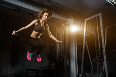 Sporty girl jumping over some boxes in a cross-training gym. Sporty girl blonde jumping over some boxes in a cross-training gym stock photography