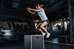 Sporty girl jumping over some boxes in gym. Sporty girl jumping over some boxes in a cross-training gym stock photo