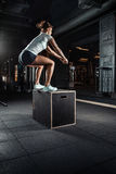 Sporty girl jumping over some boxes in gym. Sporty girl jumping over some boxes in a cross-training gym royalty free stock photos