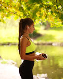 Sporty girl listens to music in headphones in autumn park Royalty Free Stock Photo