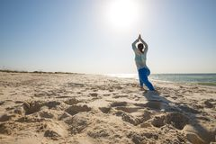 Sporty girl performs asana of yoga, stretching her hands to the. Sun, on the seashore at sunny morning, during travel. Back light and wide angle of shooting Stock Images