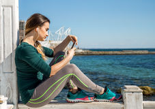 Sporty girl on the pier with the phone Stock Photo