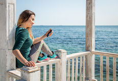 Sporty girl on the pier with the phone Stock Photos