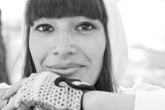 Sporty girl portrait. Black and white portrait of pretty brunette woman wearing hood and sport gauntlets, relaxing after training, smiling and looking at camera Stock Photos