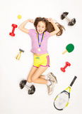 Sporty girl posing with gold medal and sports equipment Royalty Free Stock Images