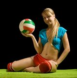 Sporty girl posing with volley-ball. On green against black Royalty Free Stock Images