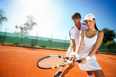 Sporty girl practice tennis with  coach. Young female sporty girl and her coach during practice tennis Royalty Free Stock Images