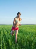 Sporty girl in red running on meadow Stock Image