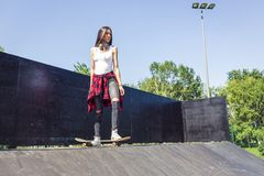 Sporty girl riding on longboard in park stock image