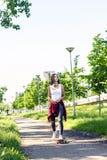 Sporty girl riding skateboards on city street stock images