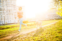 Sporty girl runing with dog. On spring lawn Royalty Free Stock Photos