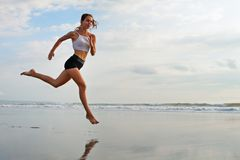 Sporty girl running by beach along sea surf royalty free stock photography