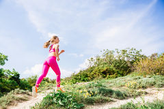 Sporty girl running in mountains. Fitness woman on nature Royalty Free Stock Photos