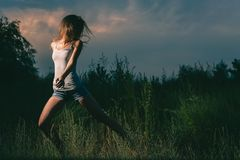 Sporty girl running in mysterious filds Royalty Free Stock Image