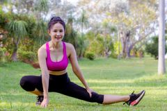 Sporty girl`s warm up exercise outdoor in the park stock photo