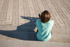Sporty girl sits on the steps in the park, resting after roller. Skating and enjoying life. A wonderful new day begins. Back view Royalty Free Stock Photo