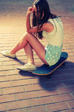 Sporty girl sitting on her skateboard and looking Royalty Free Stock Photos
