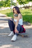 Sporty girl sitting on skateboard. Outdoors, urban lifestyle stock images