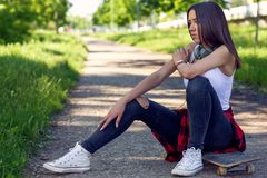 Sporty girl sitting on skateboard. Outdoors, urban lifestyle stock photo
