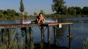 Sporty girl sitting in the splits doing stretching. Flexible sporty girl sits in the splits on a small wooden pier on the lake stock video
