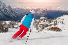 Sporty girl skiing towards the alpine hut royalty free stock photography