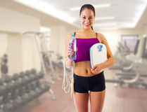 Sporty girl with skipping rope and scales at gym club Stock Image