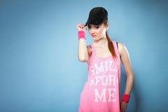 Sporty girl smiling in black baseball cap Royalty Free Stock Images