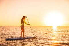 Sporty girl stand up paddle surfing with beautiful sunset or sunrise colors. Sporty young girl stand up paddle surfing with beautiful sunset Royalty Free Stock Image