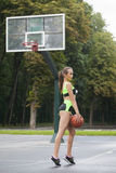 Sporty girl standing with a basketball ball Stock Photo