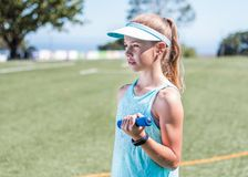 Sporty girl standing with small weight in her hand Royalty Free Stock Images